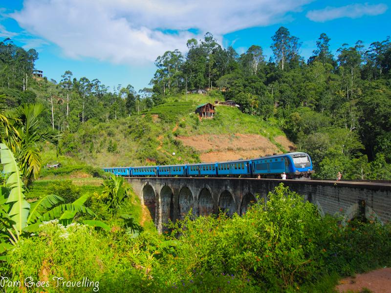 Nine arch bridge with a train leaving Ella